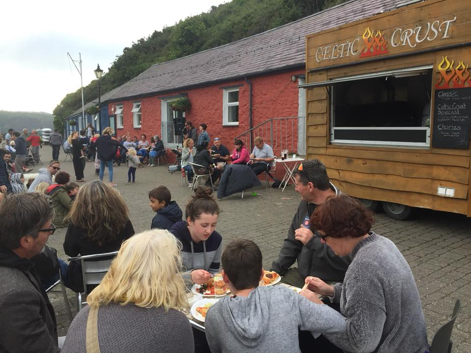 People enjoying eating pizza from Celtic Crust at the Cafe on the Quay on Father's Day Sunday June 17th with a little bit of sun shine coming through. Celtic Crust are a vegan wood fired take away pizza food truck trailer in Fishguard. Celtic Crust is available for private hire and catering.