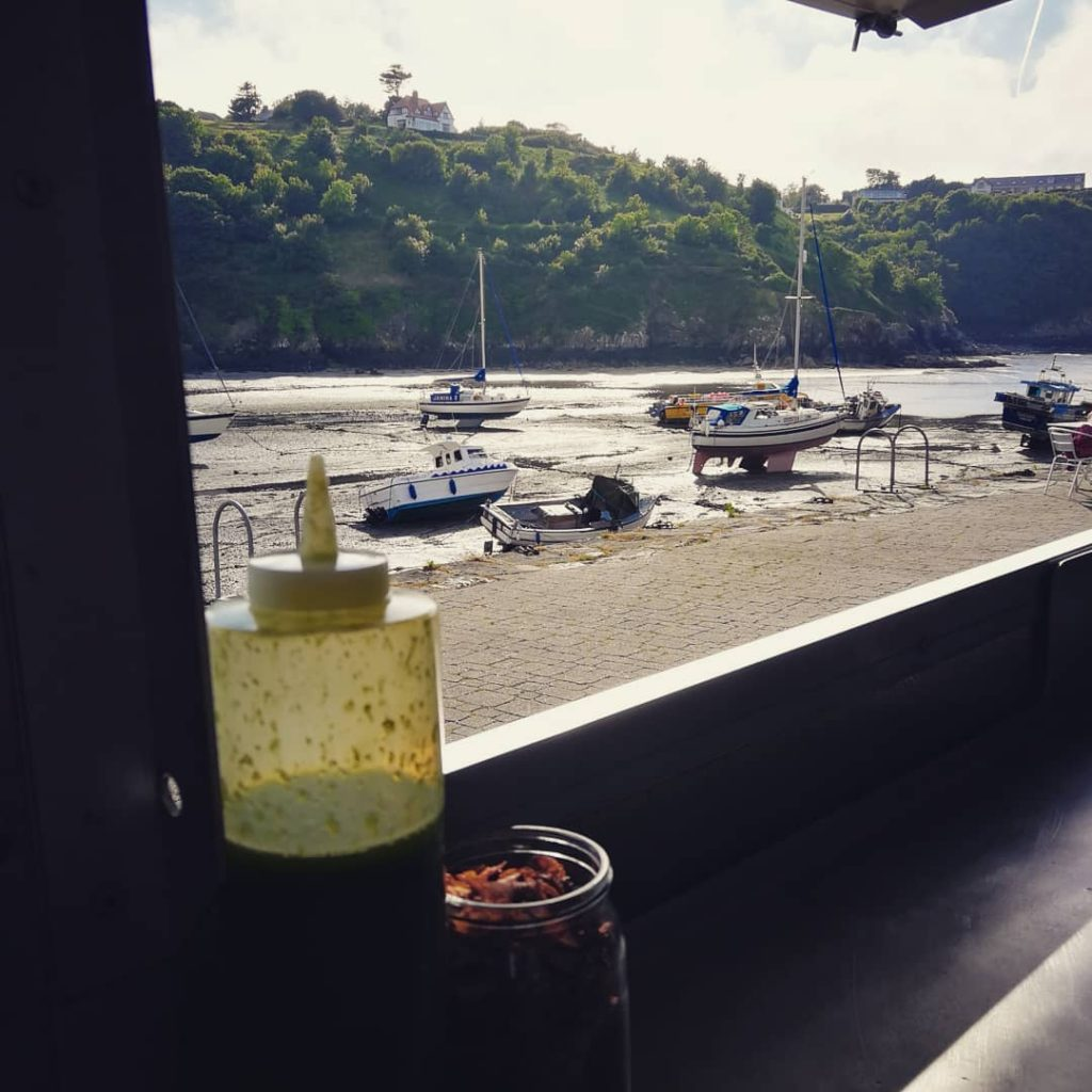 The view from the Celtic Crust wood fired vegan pizza trailer on Father's Day at Cafe on the Quay, looking out over low tide in Lower Town harbour. Celtic Crust was serving vegan pizza slices in Lower Fishguard for Father's Day along side a salad bar put on by Jo and the team from the Cafe.